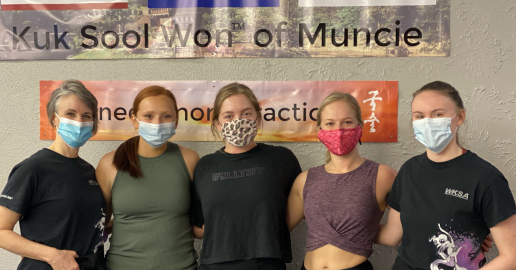 Small group of women smiling (in masks) after a self-defense course.